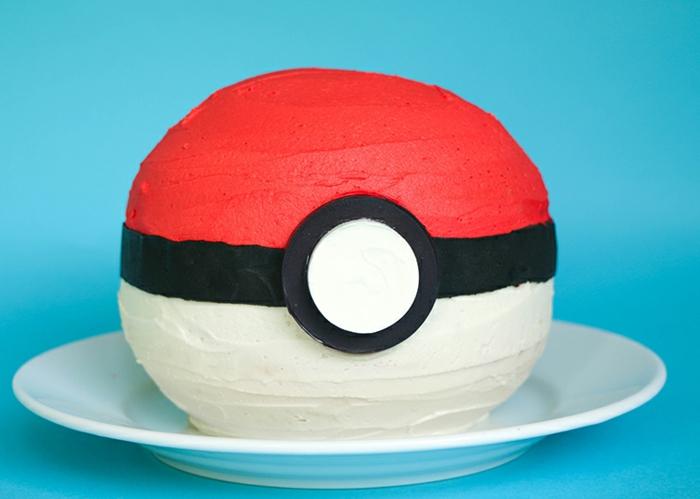 hier ist ein weißer teller und eine rote pokemon torte - diese torte sieht wie ein roter pokeball aus
