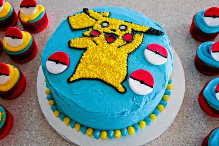 noch ein teller mit einer blauen pokemon torte mit pikachu und kleinen roten pokebällen und pokemon kuchen