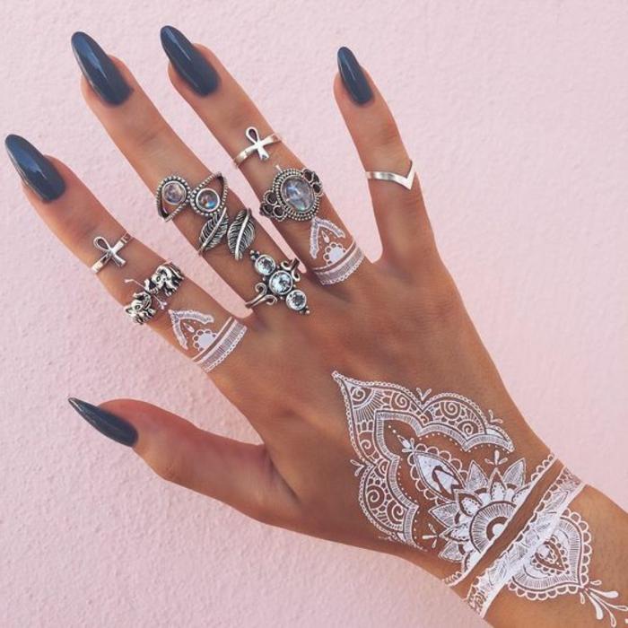eine Hand mit vielen Ringen aus Silber, weiße Fingertattoos, Handoberflächentattoo aus weißem Henna