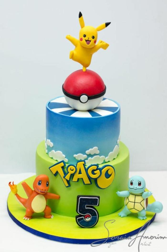 eine idee für eine zweistöckige torte mit einem roten pokeball, wolken, gelben überschriften, drei kleinen pokemon wesen und pikachu