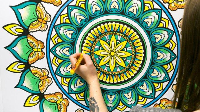 ein Mädchen malt ein riesiges Mandala mit Farbstiften aus, Schmetterlinge malen, Gelb, Orange, Blau, Grün