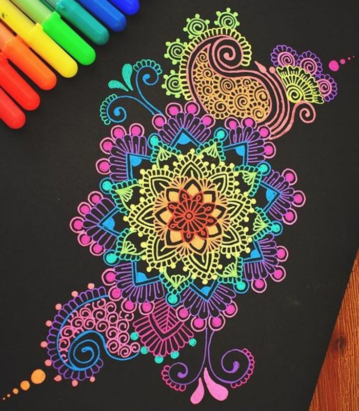 schöne Mandalas mit Neonfarben, Neon-Farbstifte, schwarzes Karton, schwarzer Hintergrund, Holztisch