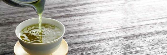 gesunde Ernährung, richtige Ernährung, grüner Tee in einer weißen Tasse auf einem Holztisch