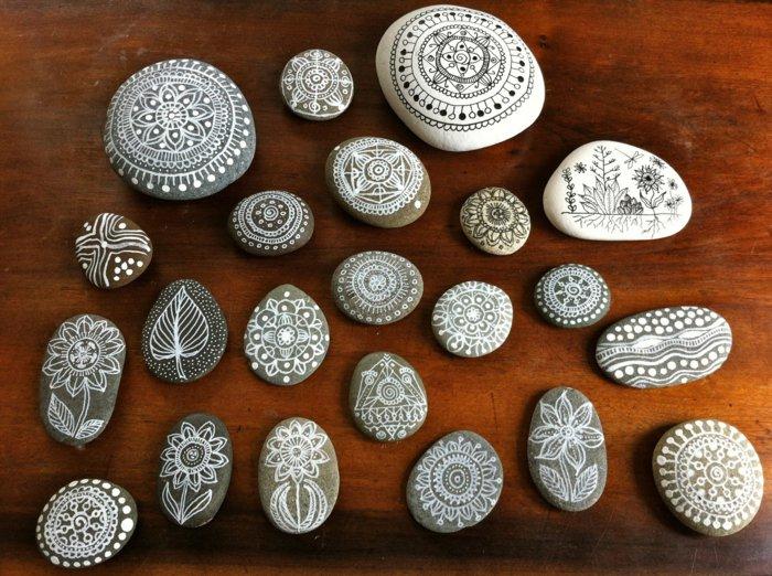 weiße und graue Steine mit Mandala-Zeichnungen bemalen, große und kleine Steine, Holztisch