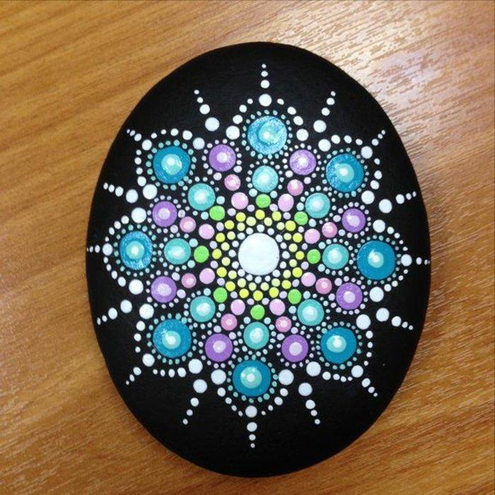 Mandala-Bild auf schwarzem Hintergrund, Schablone in der Form eines Eis, weiße, blaue, gelbe, grüne, lila und rosa Rafbe