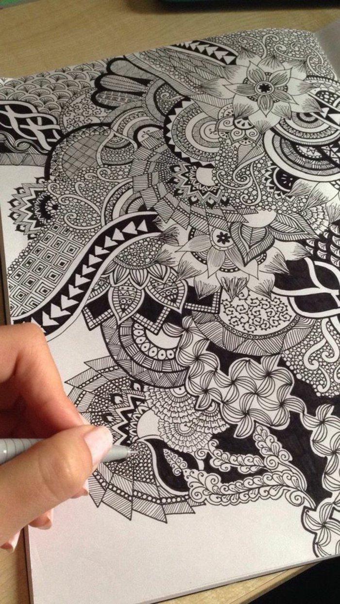 Mandala Vorlagen, Bilder zum ausmalen, eine malende Frau mit weißem Nagellack, Schreibtisch aus Holz
