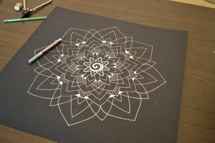 graues Malpapier, graues Karton, weiße Zeichnung mit vielen einfachen Linien und einer Spirale in der Mitte, Zirkel, Bleistifte