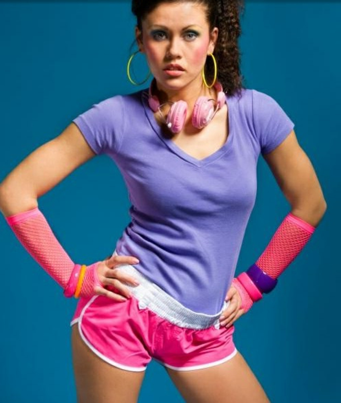 Frau aus den 80er Jahren in Sportoutfit, kurze neonpinke Hose, lila T-Shirt, Plastikarmbänder, Netzhandschuhe