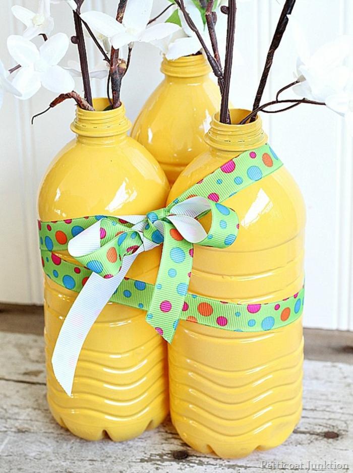 gelbe vasen mit grüner schleife us flschen, äste, blumen