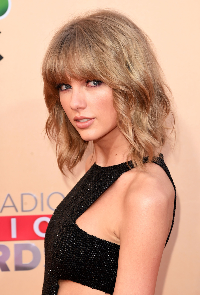 Taylor Swift, überschulterlanger Bobschnitt mit Pony, elegante Locken, dunkelblonde Haare