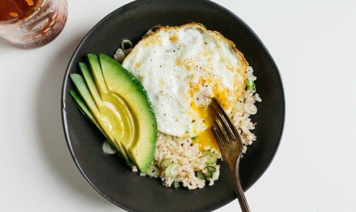 avocado auf brot oder auf reis ausgewogene ernährung mit avocado reis spiegelei mit flüssigem eigelb