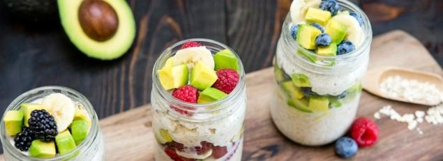 avocado stücke in dem haferflocken mix eifügen banane himbeere blaubeeren nüsse yogurt kokosnuss