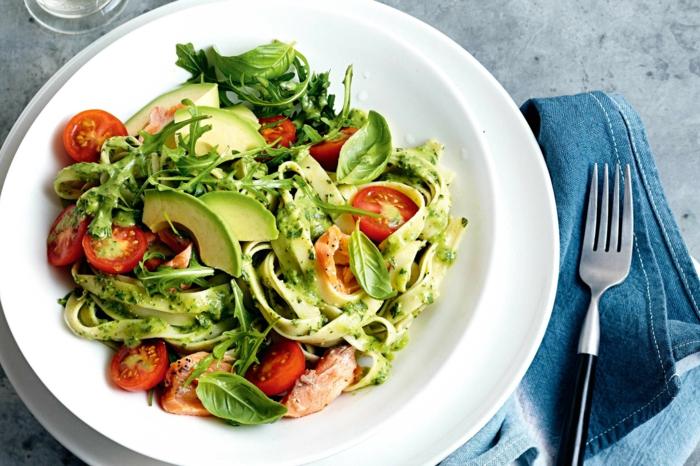 avocado mit pasta und tomaten basilikum tagliatelle mit pesto und tomaten avocado soße gabel blaue serviette