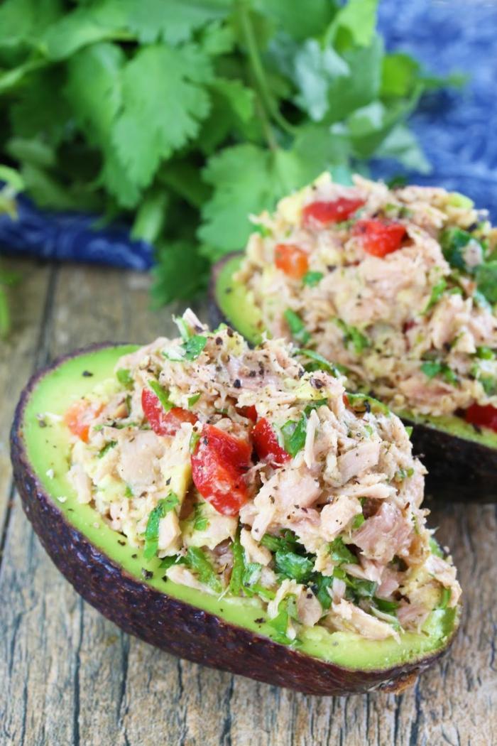 avocado zum frühstück avocadostücke avocadohälfte voll mit tunfisch und gemüse paprika petersilie ideen