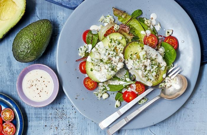 avocado rezepte salat aus avocado mit cherry tomaten ruccola yoghurt soße löffel und gabel grüner blattsalat