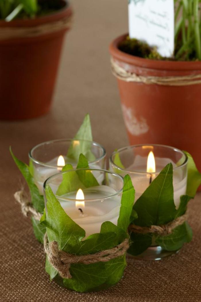 kerzenhalter aus glas dekoriert mit grünen blättern, diy deko, tischdeko
