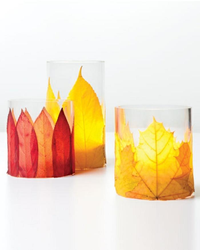 kerzenhalter aus glas dekoriert mit herbstblättern in verschiedenen farben