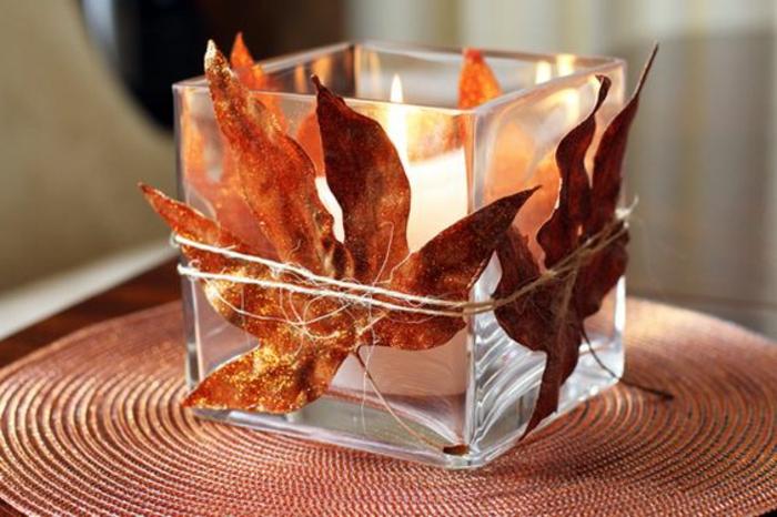 eckiger kerzenhalter aus glas, leinenschnur, getrocknete herbstblätter