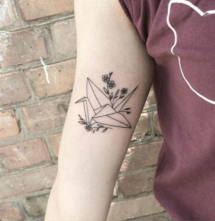 hier ist eine hand miit einem kleinen schwarzen origami tattoo - eine fliegende origami taube und kleine blumen