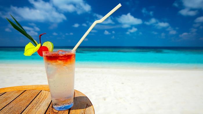 Cocktail mit Zitrusfrüchten, das Meer als Hintergrund, ein erfrischendes Getränk und die Sonne genießen