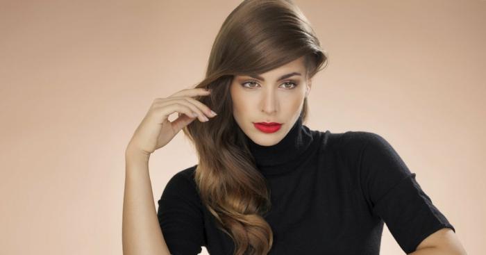 eine Frau mit langen dunklen Haaren, die gerne schicke Frisuren trägt, leicht gewellte Haare, schwarze Polobluse
