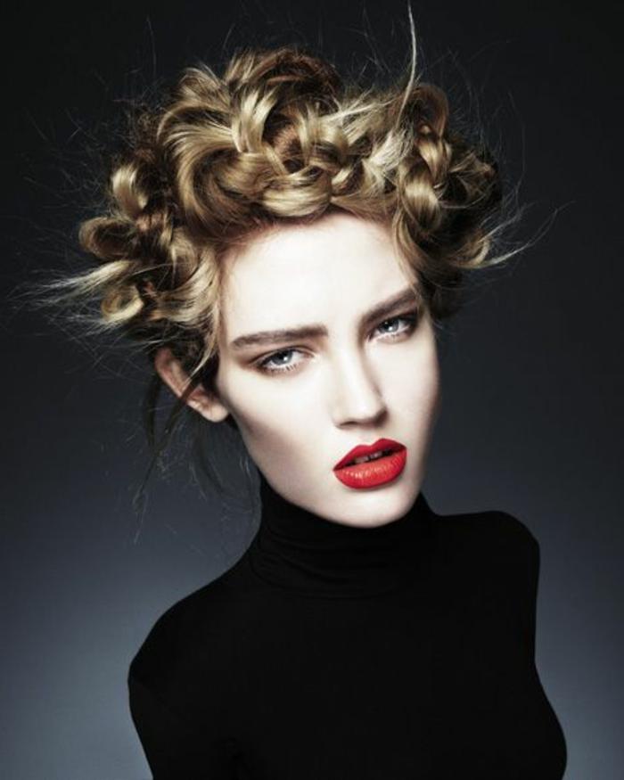 junge Frau mit weißer Haut und blonden Haaren mit einer Flechtfrisur, schwarze Polobluse, roter Lippenstift