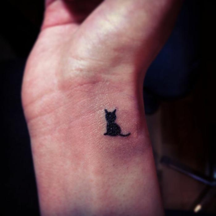 idee für einen kleinen schwarzen katzen tattoo auf handgelenk - hier ist eine kleine katze mit einem schwarzen schwanz