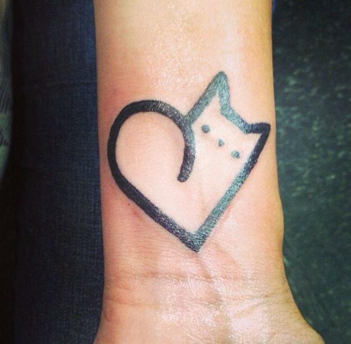 katzen tattoo auf handgelenk - eine schwarue katze mit kleinen augen und ein herz