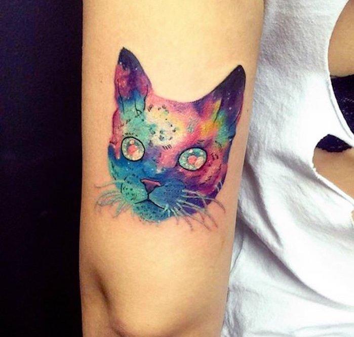 idee für eine märchenhafte tätpwierung auf der hand - eine bunte katze mit großen bunten augen