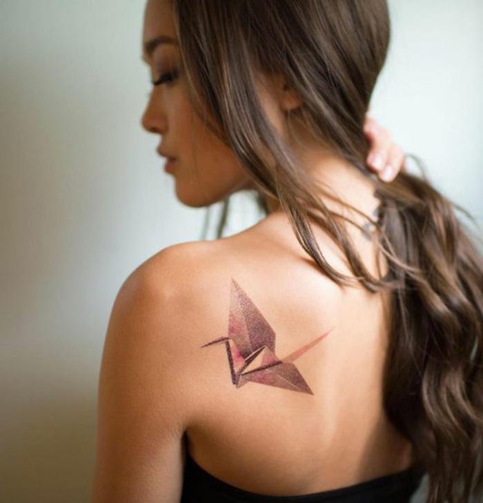 hier ist eine junge frau mit einer origami tätowierung auf dem schulterblatt - ein origami tattoo mit einem roten fliegenden origami vogel