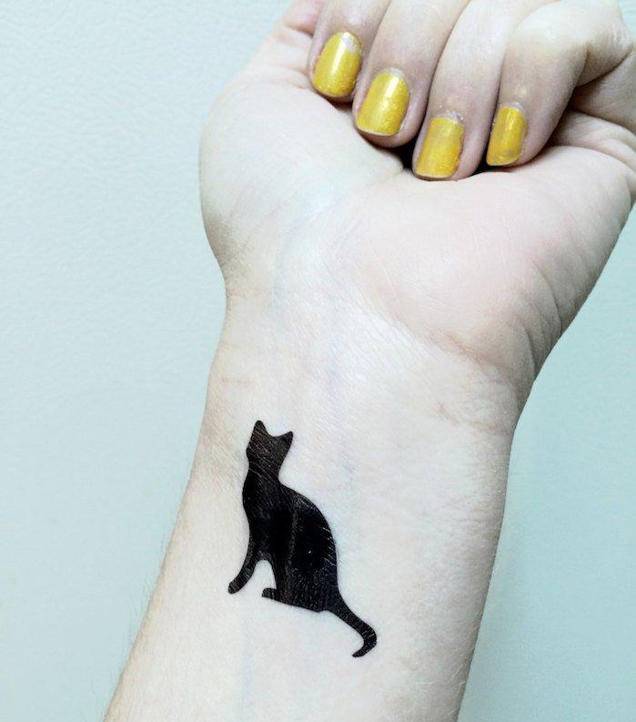 tolle idee für einen tattoo katze auf handgelenk - hier ist eine hand, gelber nagellack und eine kleine schwarze katze