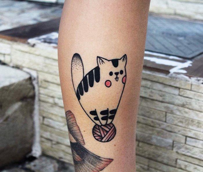 eine idee für einen tattoo katze auf bein - hier ist eine rote garnkugel und eine kleine katze mit roten backen