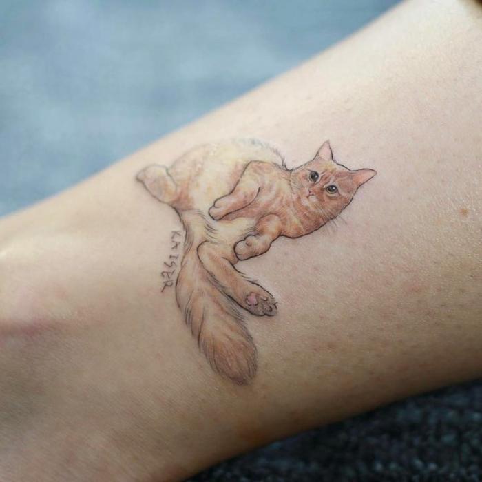 eine hand mit einem tollen tattoo katze - hier ist eine orange katze mit großen schwarzen augen