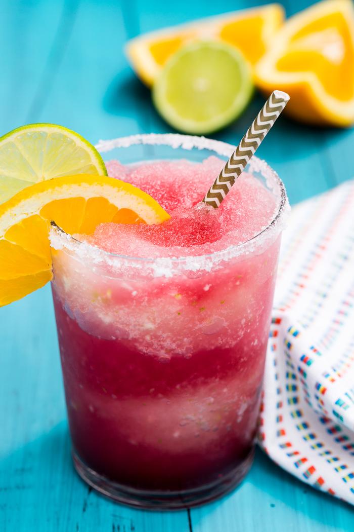 Sangria mit Beeren, kaltes Getränk für die heißen Sommertage, mit Limetten- und Orangenschnitz