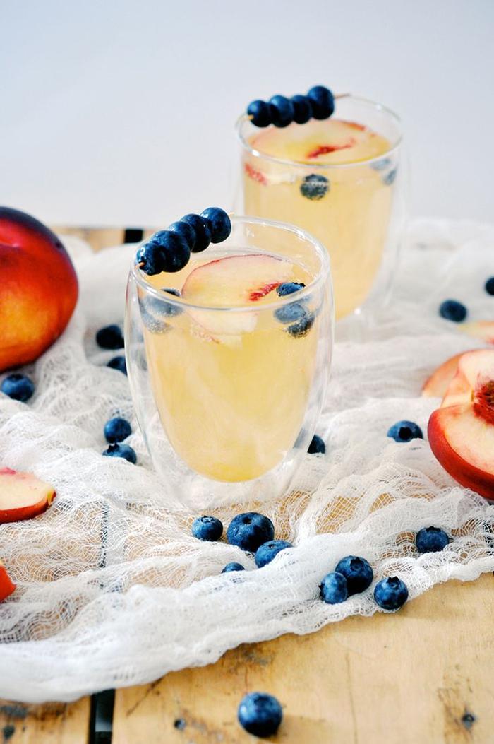 Cocktails mit Pfirsich selber machen, Gläser mit Blaubeeren dekoriert, süß und lecker