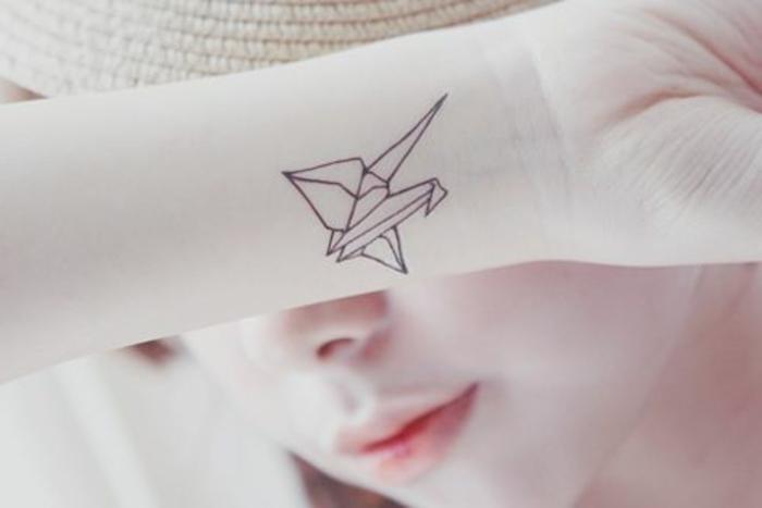 hier ist eine junge frau mit einem kleinen origami tattoo auf handgelenk - ein kleiner fliegender origami vogel auf der hand