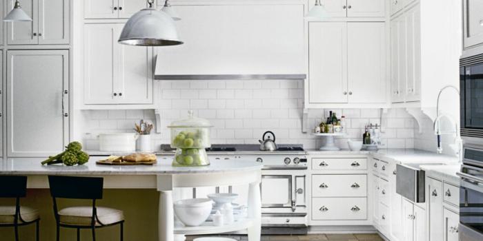 weiße Küche mit Marmor-Kochinsel, vielen Schränken in weißer Farbe und runden Metallgriffen
