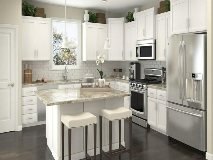 Küche in cremeweißer Farbe mit einer Frühstücksbar in der Mitte mit zwei Stühlen aus Leder