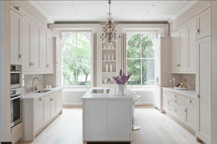 Küche, gestrichen in Weiß mit einem lila Farbakzent, Lavendelstrauß, große Küche mit Kochinsel