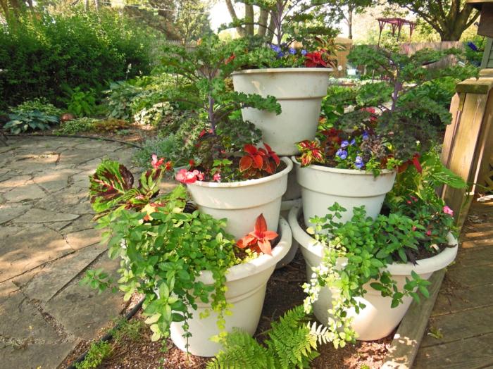weiße Blumentöpfe wie eine Pyramide geordnet - Gartenbeete gestalten