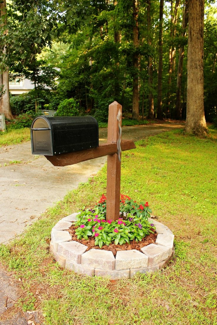 Pflegeleichtes Beet voller roten und lila Blumen um dem Briefkasten von Steinen umgeben