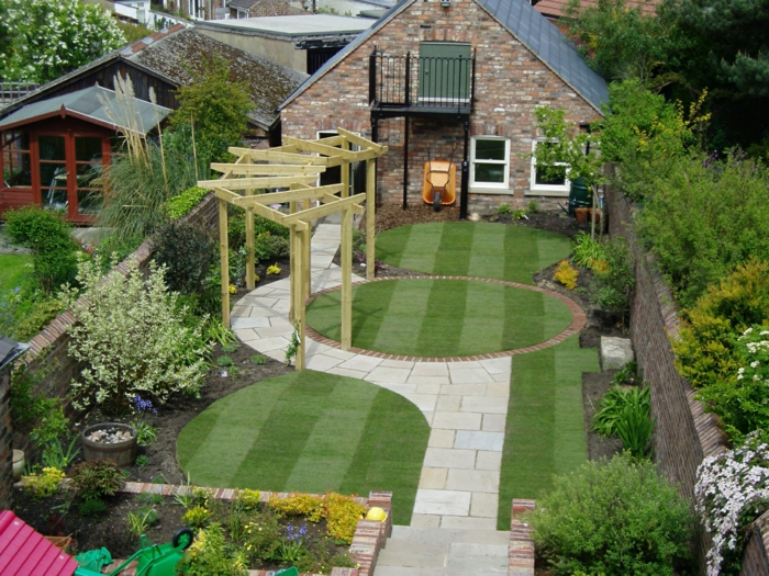 Pflegeleichte Gärten wie einem Stadium mit künstlichen Gras weiße Blumen