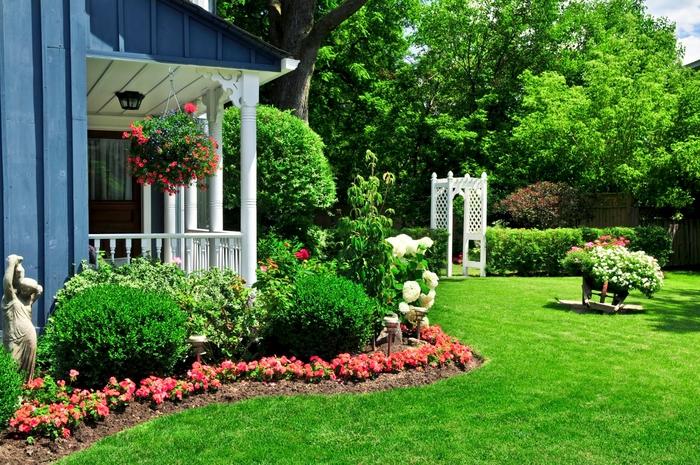 ein wunderschöner Garten mit perfektem Rasen und vielen Blumen, den Sommer genießen