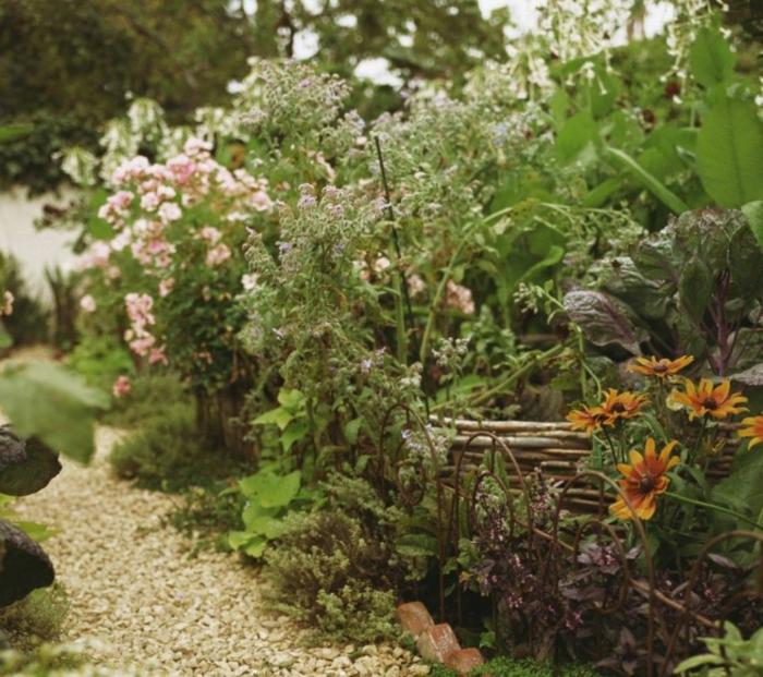 rosa und orange Blumen ein wilder pflegeleichter Garten mit einem kleinen Zaun