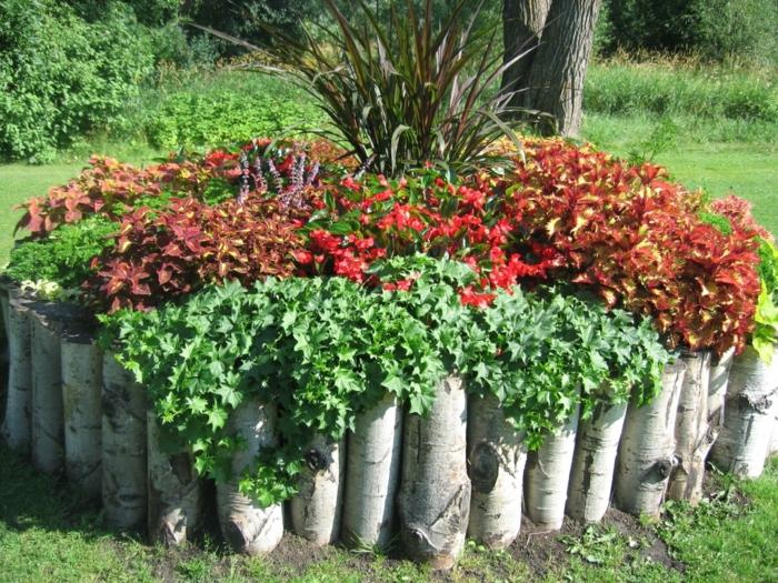 ein runder Blumentopf aus Baumstämmen voller roter Blumen - pflegeleichter Garten