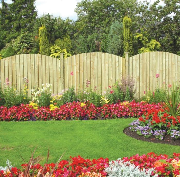 englischer Rasen, rote, gelbe und weiße Blumen - ein gerundeter Zaun - pflegeleichte Gartenpflanzen
