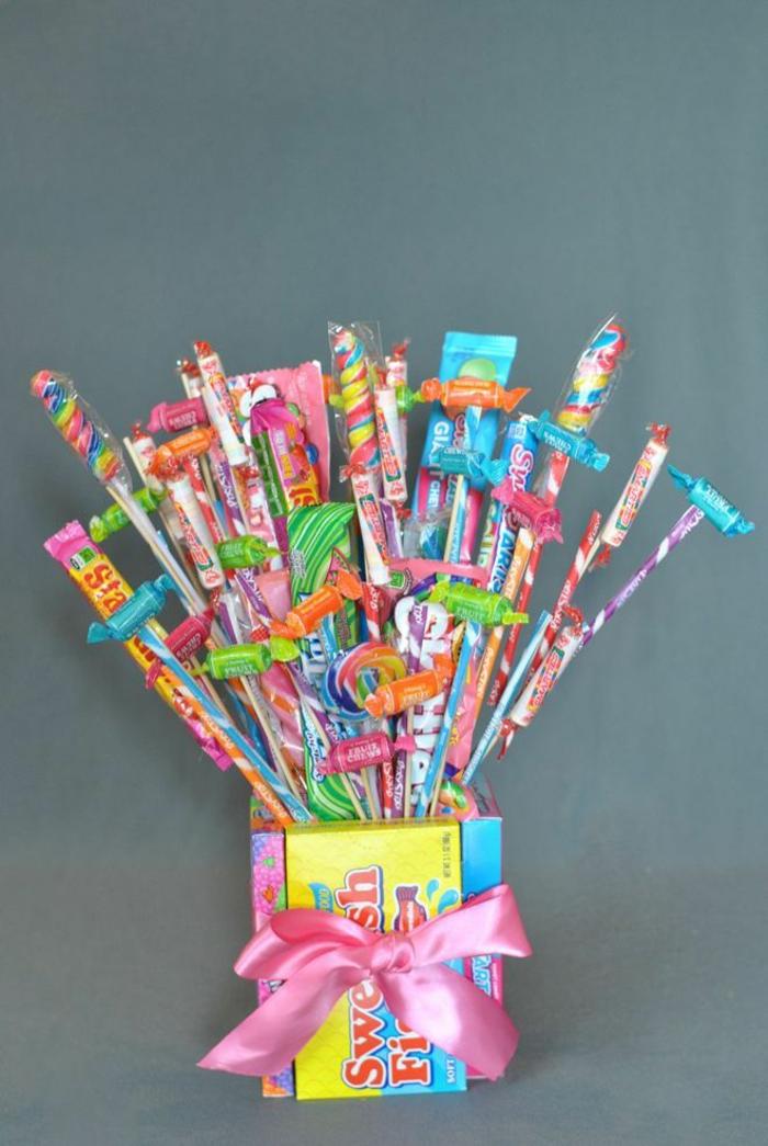 bunte Süßigkeiten auf Stocken mit rosa Band in farbenfrohe Schachtel als Korn - Geschenkkorb Ideen