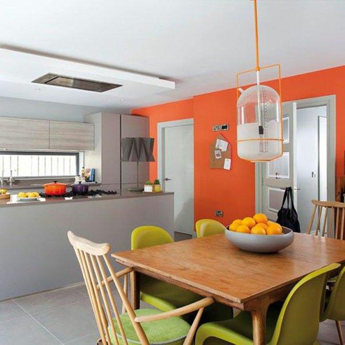 orange Wände, grüne Stühle, weiße Lampe aus Glas, graue Theke, perlgraue Küche