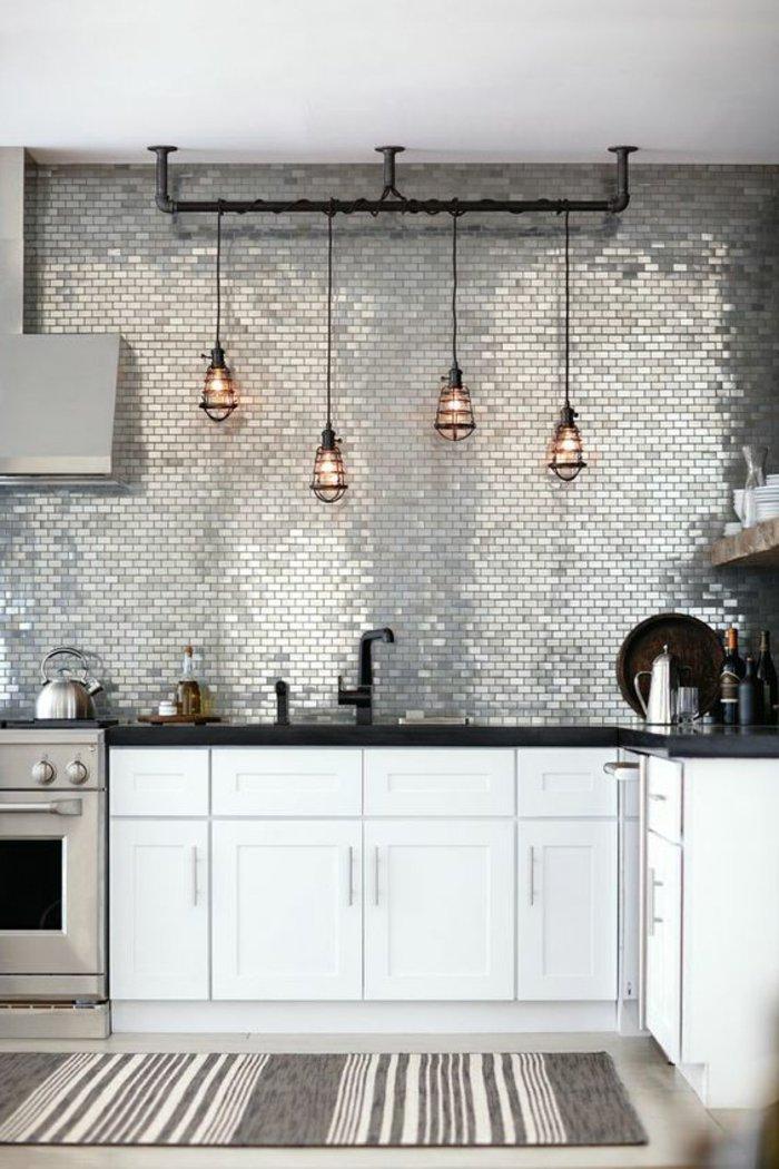 hängende Lampen, grauer Wand mit Mosaik Fliesen die Licht verspiegeln