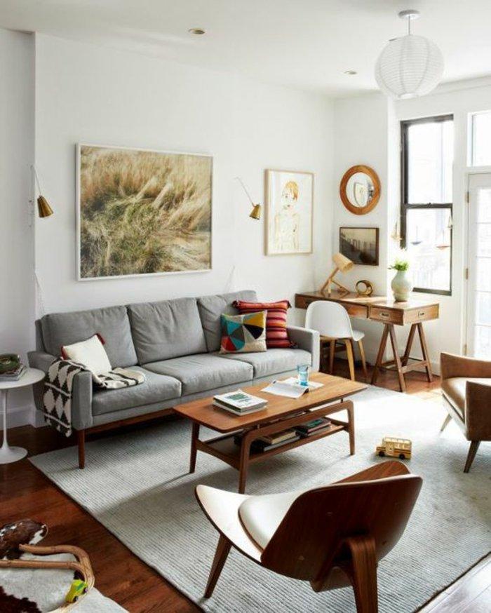 ein graues Sofa, ein abstraktes Bild, ein Bild von Mädchen, runder Spiegel - Wohnzimmer in grau